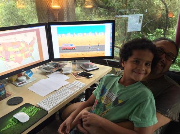 Donovan Romero, age 10, and John Romero, Brenda's husband, showcasing Donovan's own game, Gunman Taco Truck.